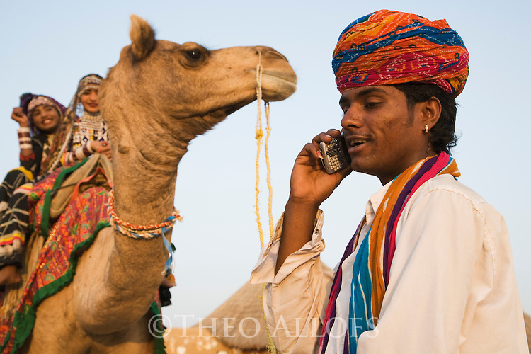 Rajasthani man on cell phone; Rajasthani dancers on camel in background; Rajasthan, India --- Model Released