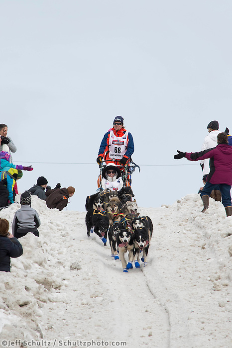 Lars Monsen and team run past spectators on the bike/ski trail with an Iditarider in the basket during the Anchorage, Alaska ceremonial start on Saturday, March 5, 2016 Iditarod Race. Photo by O'Hara Shipe/SchultzPhoto.com