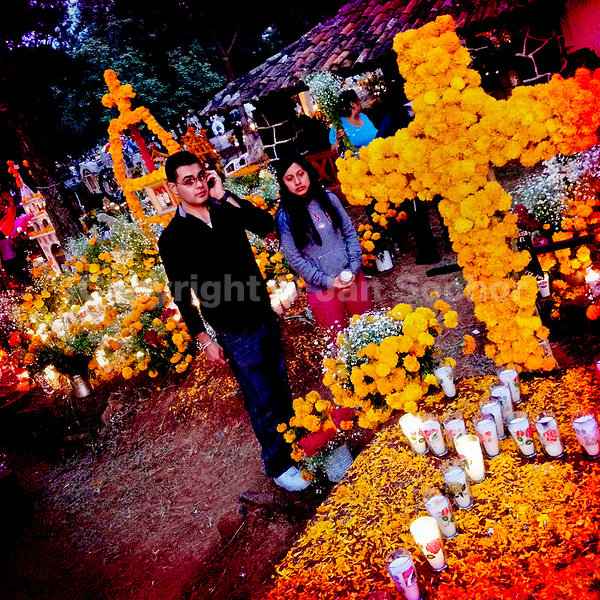 A Mexican couple stands next to a grave, covered by marigold flowers, honouring their deceased relatives during the ritual celebration of the Day of the Dead (Día de Muertos) at the cemetery of Tzintzuntzan, Michoacán, Mexico, 1 November 2014.