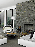The open-plan living area has contemporary modular seating and a designer armchair arranged on a rug infront of the fireplace set in a slate wall