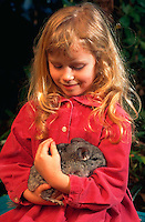 Young girl holding her unusual pet, a chinchilla.