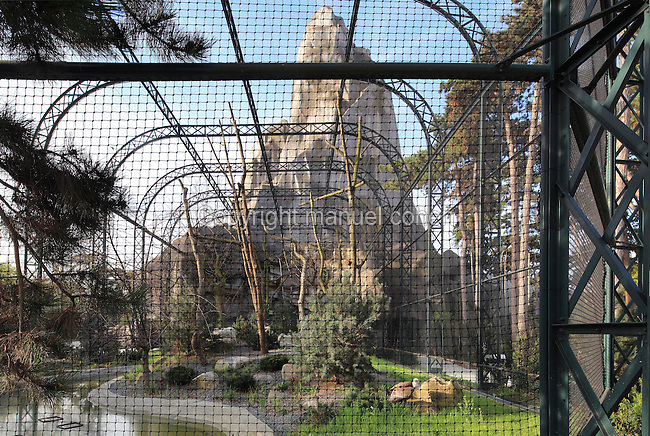 The old aviary (recently restored) and the Grand Rocher or Great Rock, with a vulture at the bottom right, in the Zone Europe, at dawn in the new Parc Zoologique de Paris or Zoo de Vincennes, (Zoological Gardens of Paris or Vincennes Zoo), which reopened April 2014, part of the Musee National d'Histoire Naturelle (National Museum of Natural History), 12th arrondissement, Paris, France. Picture by Manuel Cohen