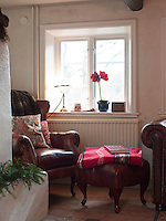 An alcove in the kitchen provides a cosy nook for a leather wing-backed chair and footstool for reading under the window