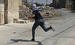 A Palestinian protester hurls a stone towards Israeli security forces during clashes following a weekly demonstration against the expropriation of Palestinian land by Israel in the village of Kfar Qaddum, near the West Bank city of Nablus on September 20, 2019. Photo by Shadi Jarar'ah