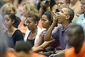 United States President Barack Obama enjoys some popcorn as he, first lady Michelle Obama and daughters Malia Obama and Sasha Obama attend the Hawaiian Airlines Diamond Head Classic men's basketball game between the Oregon State Beavers and the University of Akron Zips at the University of Hawaii at Manoa Stan Sheriff Center, Sunday, December 22, 2013. The first lady's brother, Craig Robinson, is the Oregon State University Men's Head Basketball Coach.<br /> Credit: Cory Lum / Pool via CNP