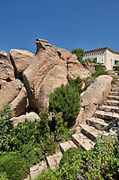 A steep flight of steps ascends to the entrance of the villa concealed behind a collection of massive rocks
