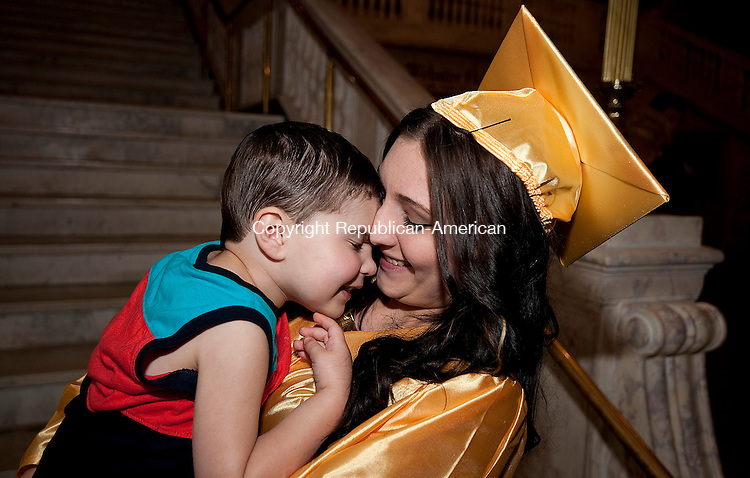 WATERBURY, CT-062014JS05--Kaynor Tech graduate Selena Valero (Fashion Technology), gets a hug from her son Eli Quiles, 2,  following graduation ceremonies Thursday at the Palace Theater in Waterbury. <br /> Jim Shannon Republican-American