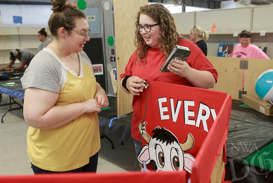 NWA Democrat-Gazette/CHARLIE KAIJO Lynlee Franks of Siloam Springs and Julie Griffin of Siloam Springs  (from left) set up their 4-H educational presentation board, Saturday, August 4, 2018 at the Benton County Fairgrounds in Bentonville. They are educating the public of all the different ways a cow can be used aside from meat.<br />
