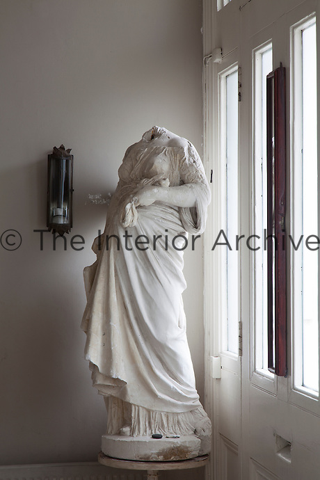 A headless statue hovers behind the front door