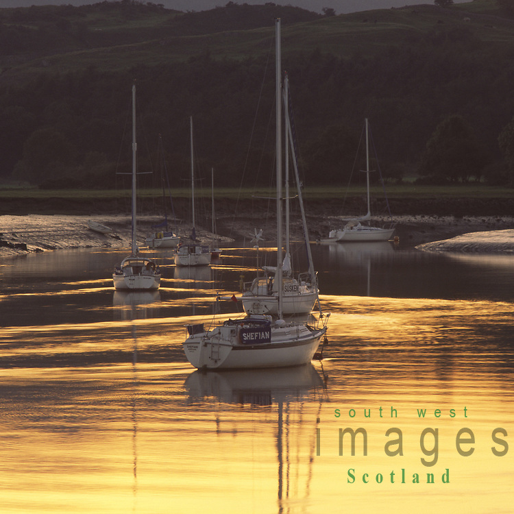 Yachts on a sea of gold sunset light reflected on the River Urr at Kippford on the Solway Firth coast Scotland UK