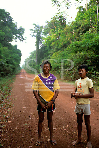 Mato Grosso, Brazil. Rikbaktsa (Canoeiro) Indian man in Brazilian flag motif t-shirt and his son.