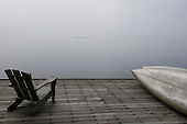 Eagle Bay, New York. Big Moose Lake. The Waldheim (vacation resort in the style of the traditional Adirondack great camps). Chair on dock with kayaks at dawn with early morning mist. ID: AJ-DC. © Ellen B. Senisi