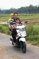 Borobudur, Java, Indonesia.  Family Riding Motorbike on Rural Road, no Helmets.