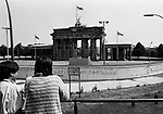 People on a viewing platform looking down on a section of the Berlin Wall at the Brandenburg Gate, seen from the western side of the divide. The Berlin Wall was a barrier constructed by the German Democratic Republic (GDR, East Germany) starting on 13 August 1961, that completely cut off West Berlin from surrounding East Germany and from East Berlin. The Wall was opened on 9. November 1989 allowing free movement of people from east to west.