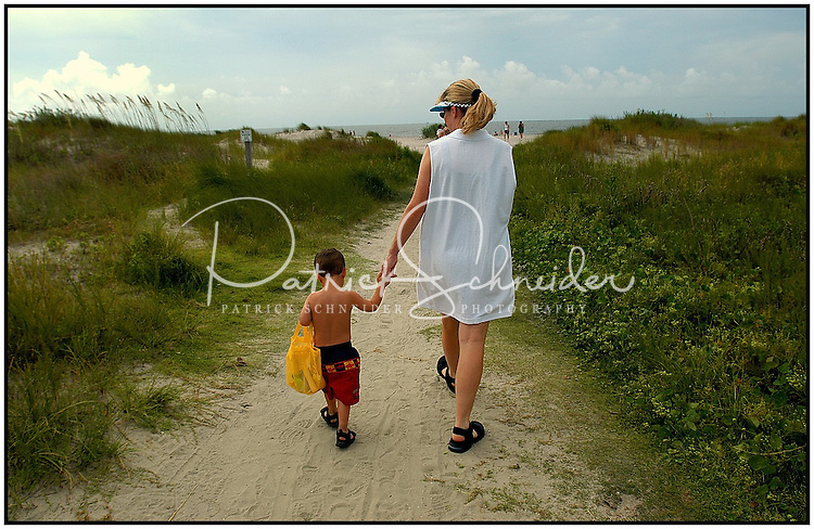A young boy heads with his mother off to the beach along a sandy path. Photo taken on Sullivan's Island near Charleston, SC.   Model released image may be used to illustrate other destinations or concepts.