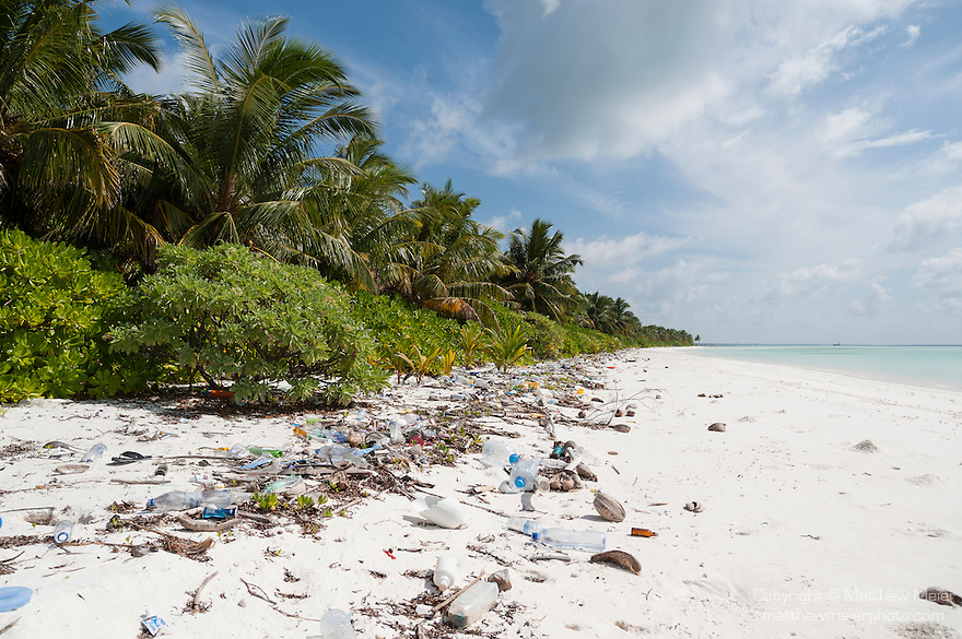 Baresdhoo Island, Laamu Atoll, Maldives; plastic trash or marine debris sitting on a deserted, white sand beach in the Maldives, on a beautiful sunny afternoon with blue skies and puffy white clouds