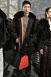 Detail of model Sehan Lee posing in an oversided rabbit fur bomber with fox collar and nylon sleeves, mesh tee, black velvet sweapant and black rabbit fur gym bag with orange nylon, from the Adrienne Landau Fall Winter 2016 collection, presented on February 17 2016, during New York Fashion Week Fall 2016.