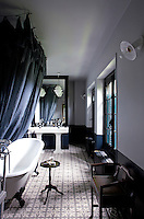 The bathroom is furnished with a free-standing roll-top bath and a double pedestal wash basin