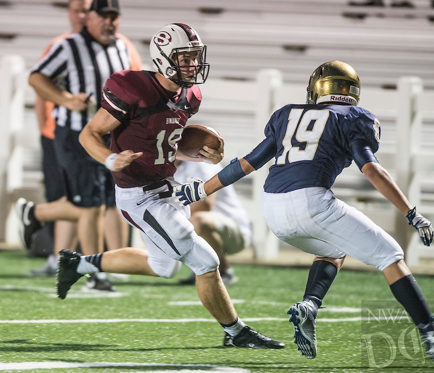 STAFF PHOTO ANTHONY REYES &bull; @NWATONYR<br /> Fuller Chandler, left, Springdale High junior, rushes as CJ Bottorff, Shiloh Christian junior, defends Monday, Aug. 25, 2014 in a scrimmage at Bulldog Stadium in Springdale.