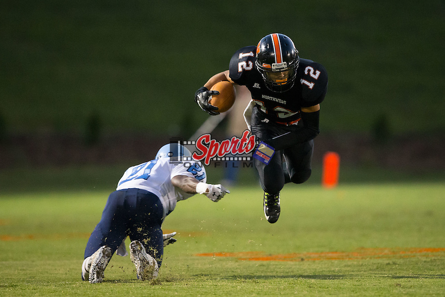 Nathan Clark (12) of the Northwest Cabarrus Trojans flies through the air after being tripped up by JT Sanders (21) of the West Rowan Falcons at Trojan Stadium September 19, 2014, in Concord, North Carolina.  The Falcons defeated the Trojans 13-0.  (Brian Westerholt/Sports On Film)