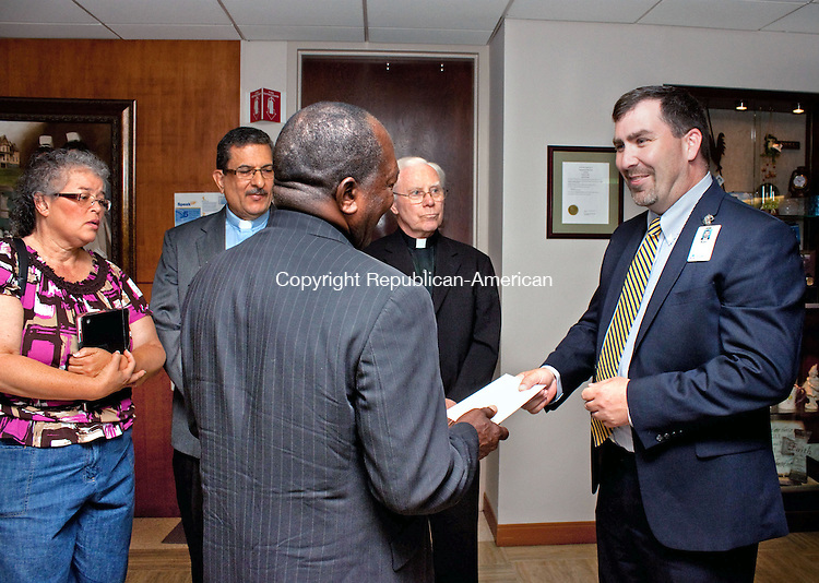 WATERBURY - JUNE 18 2014 061814DA01- Member of the Naugatuck Valley Project, Bishop Lionel French hands a letter to Director, Safety &amp; Security Ryan B. LaFleur, right, at Waterbury Hospital on Wednesday, seeking discussion with chairman of the board about preserving community benefits after takeover by for-profit Tenet Healthcare Corp. Along with French are other members, from back left, organizer Elizabeth Rosa, Pastor Jose Rosa and Father John Cooney.<br /> Darlene Douty Republican American