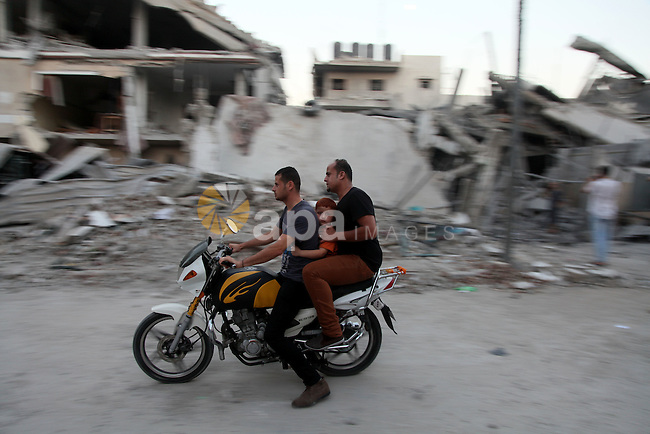 Palestinians ride a motorcycle past a destroyed house as they leave their home in the Jabalia refugee camp in the northern Gaza Strip on August 8, 2014. Israel launched air strikes across the Gaza Strip on Friday in response to Palestinian rockets fired after Egyptian-mediated talks failed to extend a 72-hour truce in the month-long war. Photo by Ezz Zanoun