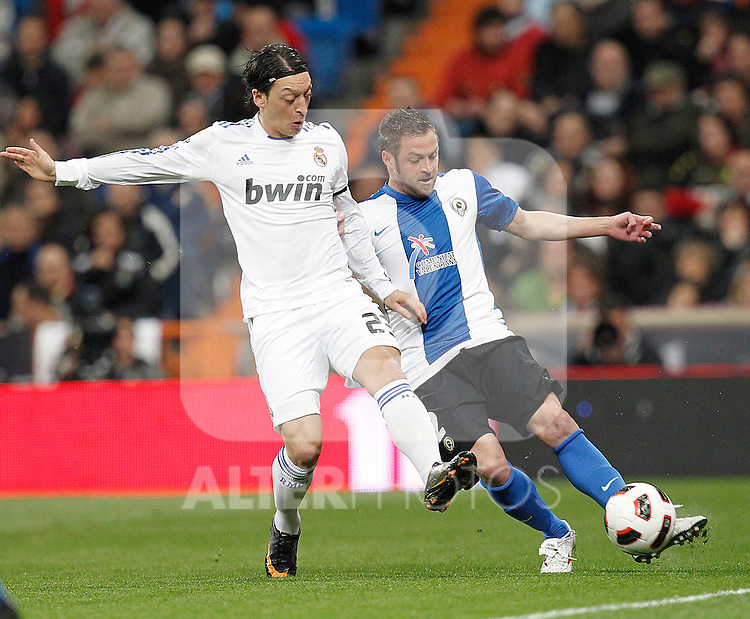 Real Madrid's Mesut Ozil and Hercules' Pulhac during la liga match on March 12, 2011...Photo: Cesar Cebolla / ALFAQUI