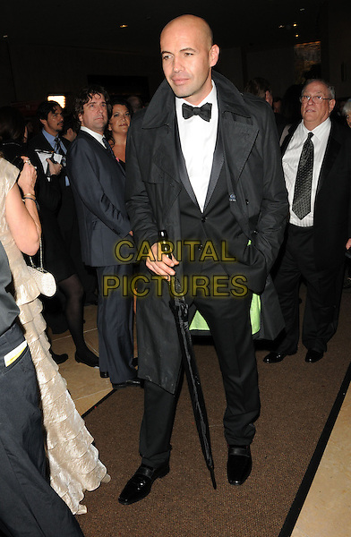 BILLY ZANE.Leaving the 67th Golden Globes held at The Beverly Hilton Hotel in Beverly Hills, California, USA..January 17th, 2010 .departures full length black tuxedo umbrella coat hand in pocket globe.CAP/DVS.©Debbie VanStory/Capital Pictures