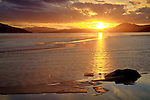 Idaho, North, Bonner County, Sandpoint. Ice thaws on Oden Bay of Lake Pend Oreille under a golden  sunset.