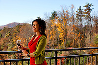 A woman, holding a glass of wine, looks out over the Blue Ridge Mountains from a balcony in Asheville NC's Biltmore Park Town Square, a planned community of residential living, office spaces and shopping.