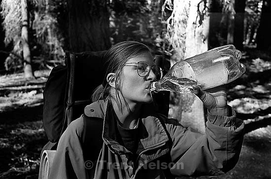 Laura Nelson drinking water while backpacking at Sword Lake.<br />