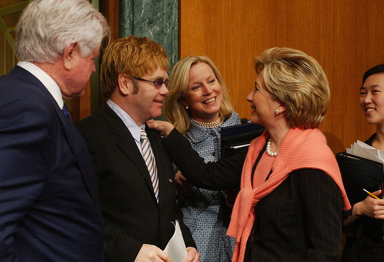 john2/041102 - Musician Elton John greets Sen. Hillary Clinton, D-N.Y., right, before testifying on the world wide AIDS epidemic in front of the Senate Health, Education, Labor and Pensions Committee.  John is the chairman of the Elton John AIDS Foundation.  Also pictured is Sen. Ted Kennedy, D-Mass., and Sandy Thurman, president of the International AIDS Trust.