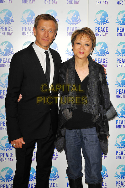 Jeremy Gilley and Judy Cheng.Peace One Day, Wembley Arena, London, England. .21st September 2012.half 3/4 length white black suit shirt tie grey gray cardigan top jeans denim.CAP/MAR.© Martin Harris/Capital Pictures.