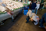A visitor looks over at a Monk fish at the Pike Place Fish Company in Seattle.  For over a century a century, the Pike Place Market, has become a city institution and a national attraction, bringing in over a million tourists a year. .Jim Bryant Photo. ©2010. ALL RIGHTS RESERVED.