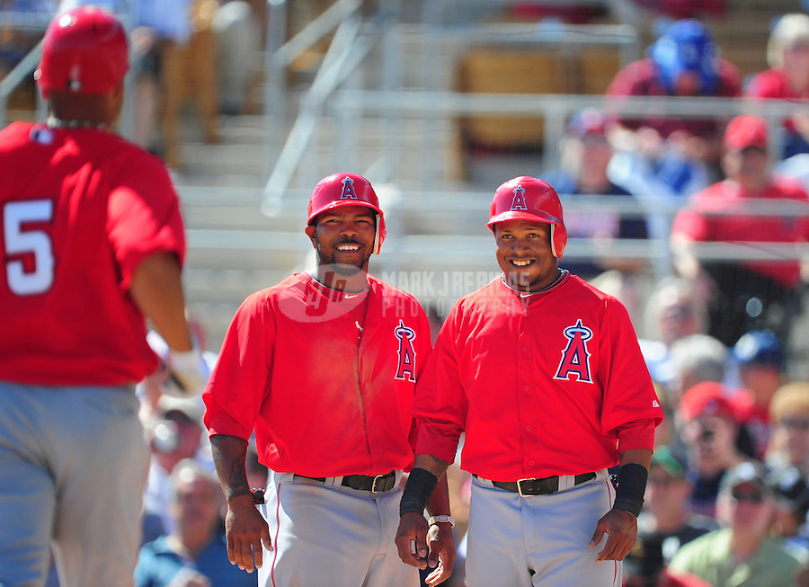 Mar. 14, 2012; Phoenix, AZ, USA; Anaheim Angels players Erick Aybar (right) and Howie Kendrick (center) wait to congratulate first baseman Albert Pujols as he rounds the bases after hitting a three run home run in the third inning against the Chicago White Sox at The Ballpark at Camelback Ranch. Mandatory Credit: Mark J. Rebilas-