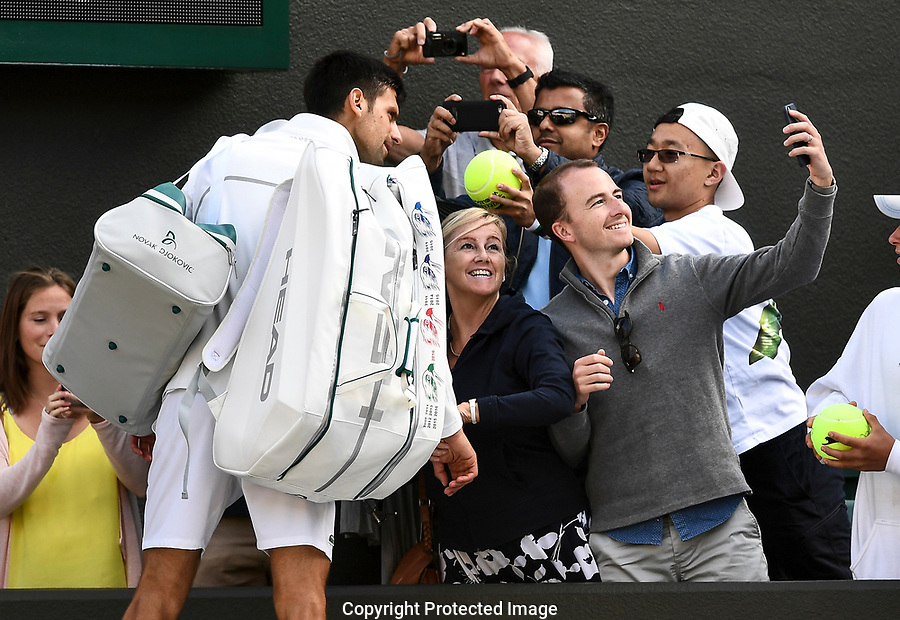 Novak Djokovic (SRB) stops for a photograph as he leaves court following his retirement