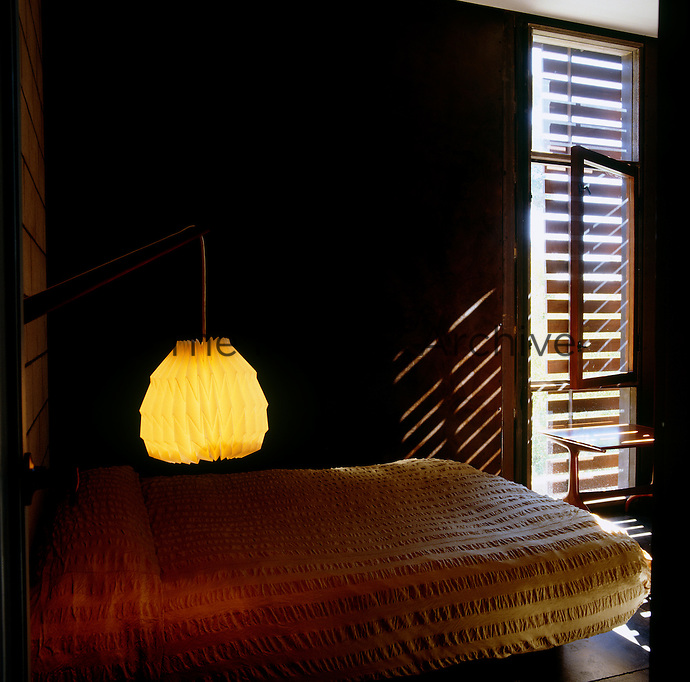 The simple bedroom is lit by a pendant light that resembles a Chinese lantern