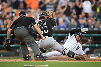 Chicago White Sox catcher Kevan Smith (36) fields a throw as Nick Castellanos (9) of the Detroit Tigers slides across home plate while umpire Mark Carlson looks on at Comerica Park on June 2, 2017 in Detroit, Michigan.  The Tigers defeated the White Sox 15-5.  (Brian Westerholt/Four Seam Images)