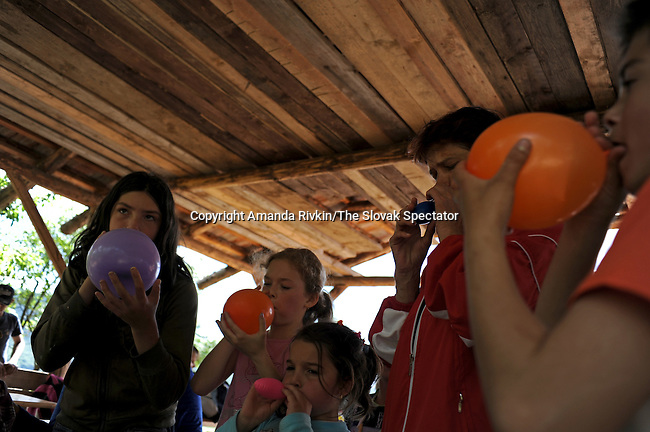Children participate in a balloon blowing contest at a celebration for international children's day in Jablonov Nad Turnou, Slovakia on June 5, 2010.