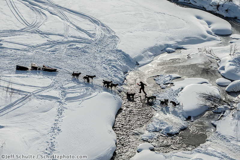 An Iditarod musher walks his dogs across a stretch of open water of the Happy River on the trail in the Alaska Range in Ptarmigan Valley on the way to Rohn from the Rainy Pass checkpoint during Iditarod 2016.  Alaska.  March 07, 2016.  <br /> <br /> Photo by Jeff Schultz (C) 2016 ALL RIGHTS RESERVED