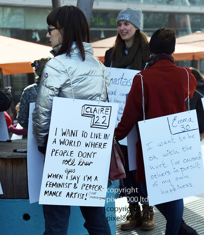 Pic shows: What women want -  Live Art show on Southbank today  by Brutally Honest  art group<br /> part of Women Of World  conference.<br /> <br /> Women encouraged to write placards and describe what they want.<br /> <br /> Anything from world peace to a shed.<br /> <br /> <br />  project was inspired by a man called Robert Darling, who has spent 12 years, standing in Times Square twice a week wearing a sandwich board asking for a wealthy wife. To our knowledge he is still out there, plugging away.<br /> <br /> We first piloted our own version of this in 2014, and are excited at the prospect of staging this simple concept in as many different cities and countries with different communities of people, over the coming years.<br /> <br /> <br /> <br /> Pic by Gavin Rodgers/Pixel 8000 Ltd