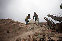 Nepalese men remove the rubble from their destroyed house in Shanku near Kathmandu, Nepal. May 9, 2015