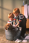 Twin boys in overalls washing cocker spaniel.