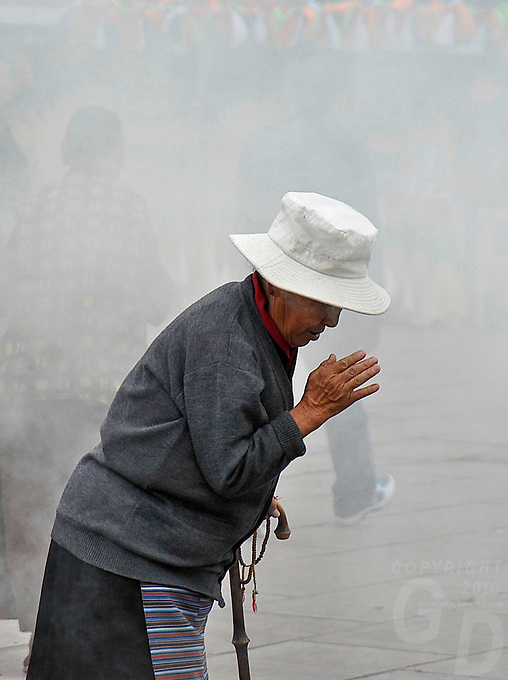 The central part of Barkhor street is covered in smoke, pilgrims burning their incense in giant Burners right in front of Jokhang Temple,Lhasa.The Jokhang Temple is one of Tibet's holiest shrines, originally built in 647 A.D. in celebration of the marriage of the Tang Princess Wencheng and the Tubo King Songtsen Gampo. In front of the gate is a stone Tablet of Unity from the Tang Dynasty; inscribed are both Chinese characters and Tibetan script. Nearby is the stump of the willow tree said to have been planted by Princess Wencheng herself; two younger willow trees now flank the stump of the first tree...Located in the center of old Lhasa, the temple was built by craftsmen from Tibet, China, and Nepal and thus features different architectural styles. The temple is also the spiritual center of Tibet and the holiest destination for all Tibetan Buddhist pilgrims. In the central hall is the Jokhang's oldest and most precious object--a gold statue of a seated 12-year-old Sakyamuni. This is said to have been transported to Tibet by Princess Wencheng from her home in Changan in 700 A.D. Other precious antiques in the temple include a silk portrait of Buddha from the Tang Dynasty and a pearl gown and gold lamp from the Ming Dynasty. The three-leafed roof of the Jokhang offers splendid views of the bustling Barkhor market and across to the Potala Palace..