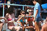 Barmaid passes tray of whiskey to bikini clad Spring Breakers.