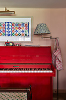 An old upright piano is given a new lease of life with a coat of bold, bright red paint.