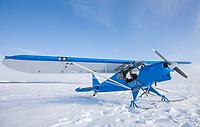 Super cub bush plane on zastrugi, wind blown snow, Seward Peninsula, Alaska.