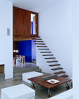 The cantilevered staircase leads up to a bedroom and bathroom which are encased in a wooden box