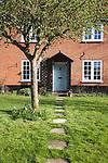 Garden path leading past apple tree to front door of house, UK