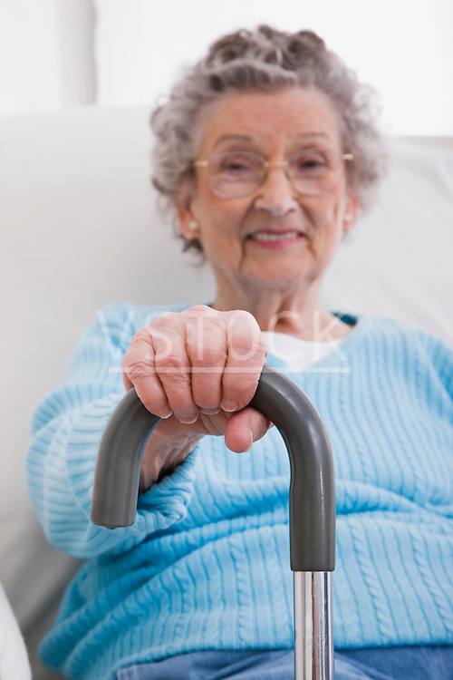 Portrait of senior woman with hand on walking cane